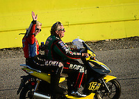 Sept. 21, 2012; Ennis, TX, USA: NHRA funny car driver Courtney Force waves to the fans while her father John Force drives the scooter during qualifying for the Fall Nationals at the Texas Motorplex. Mandatory Credit: Mark J. Rebilas-US PRESSWIRE