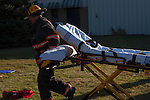 A firefighter running with a medical stretcher blurred with motion