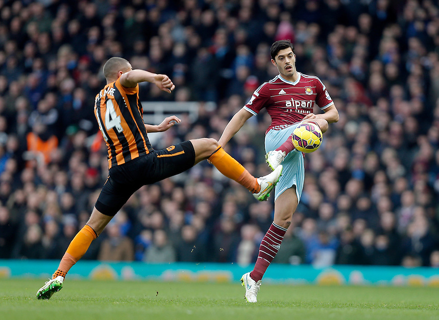 West Ham United's James Tomkins under pressure from  Hull City's Jake Livermore<br /> Photographer Kieran Galvin/CameraSport<br /> <br /> Football - Barclays Premiership - West Ham United v Hull City - Sunday 18th January 2015 - Boleyn Ground - London<br /> <br /> &copy; CameraSport - 43 Linden Ave. Countesthorpe. Leicester. England. LE8 5PG - Tel: +44 (0) 116 277 4147 - admin@camerasport.com - www.camerasport.com