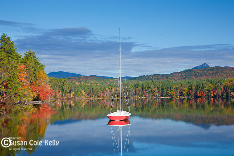 A red sailboat on White Lake, White Lake State Park, Tamworth, NH, USA