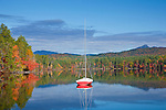 A red sailboat on White Lake, White Lake State Park, Tamworth, NH, USA