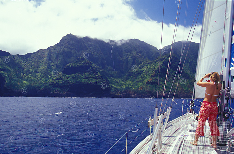 Woman looking at waterfall on Kauai's Na Pali Coast from deck of sailing yacht
