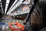 AMSTERDAM - Onder het Centraal Station in Amsterdam werkt bouwcombinatie Combinatie Strukton/Van Oord (CSO) aan het uitgraven van een twintig meter diepe zinksleuf voor de Noord-Zuidlijn. Op de plek waar later een drijvende betonnen 130 meter lange tunnelbak via het IJ wordt binnengevaren, zijn de houten palen onder het 120 jaar oude station, vervangen door twee stalen damwanden waartussen momenteel de grond wordt weggebaggerd. De betonnen platen op die wanden ondersteunen het monumentale pand, zodat daaronder bootjes en een baggerponton in een nauwe ruimte rustig hun werk kunnen doen. COPYRIGHT TON BORSBOOM