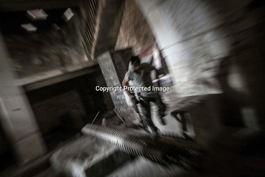 In this Monday, Oct. 29, 2012 photo, a rebel fighter belonging to the Qatebee Sokor Al-Islam sneaks through house building as he takes his fire position during clashes between rebel fighters and the Syrian army in the nearby Castel Harami battlefield in the Jdeide district of Aleppo, Syria, as heavy shelling and fighting were report during the last day of Eid celebration. (AP Photo/Narciso Contreras).