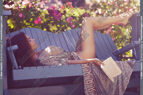 Sensual portrait of a beautiful sexy half naked young woman sleeping lying down on a bench in a rose garden with a book in her hand