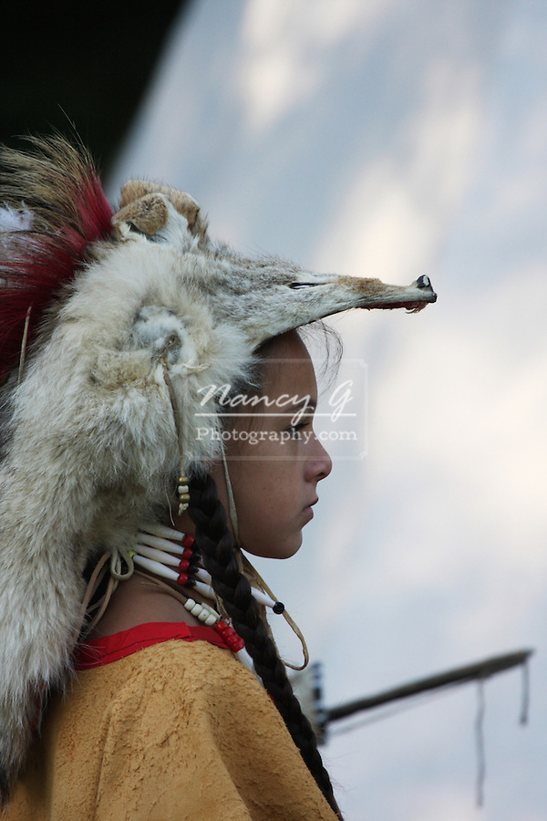 A Native American Indian boy wearing traditional leather dress and a coyote skin fur hat headress