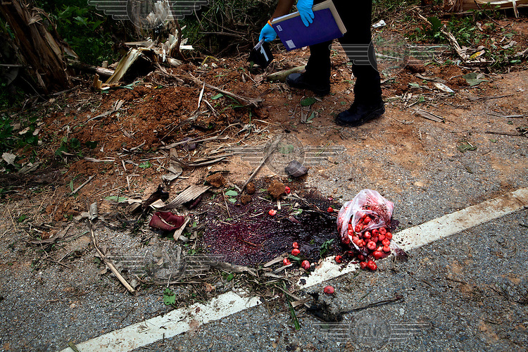A pool of blood, discarded bandages and a bag of fruit are seen as a Forensic Police officer investigates the site of a bomb that had recently gone off killing one Ranger and wounding two others in Kradoh Village near Pattani. /Felix Features