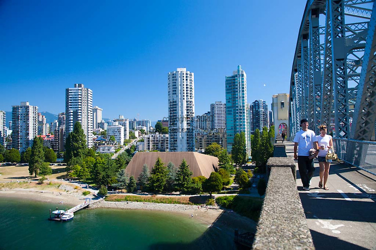 A couple crosses the pedestrian and bike friendly Burrard St. Bridge which spans English Bay.  A water taxi stand is below the bridge and downtown Vancouver is in the background.