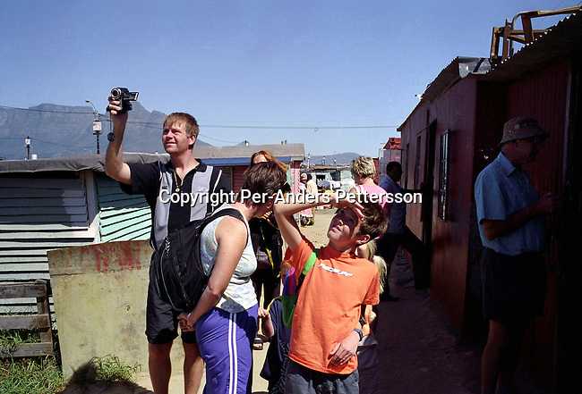 LANGA, SOUTH AFRICA - FEBRUARY 25 : .Foreign tourists take pictures while on a township tour on February 25, 2004 in Langa, a poor township outside Cape Town, South Africa. The country has seen a big increase of visitors since the fall of Apartheid and democratic election in 1994. Many tourists are interested in visiting the poor townships outside Cape Town, where millions of people live in appalling conditions without running water or electricity.   .(Per-Anders Pettersson/Getty Images).