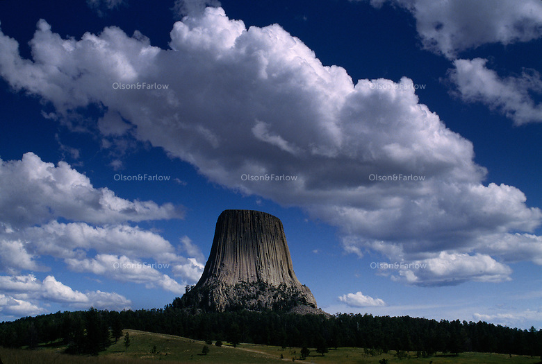 Puffy white clouds and blue skies over Devils Tower an ancient volcano plug  or monolithic igneous intrusion that is more than 1200 feet high. It was featured in the Hollywood movie Closer Encounters of the Third Kind in 1977.