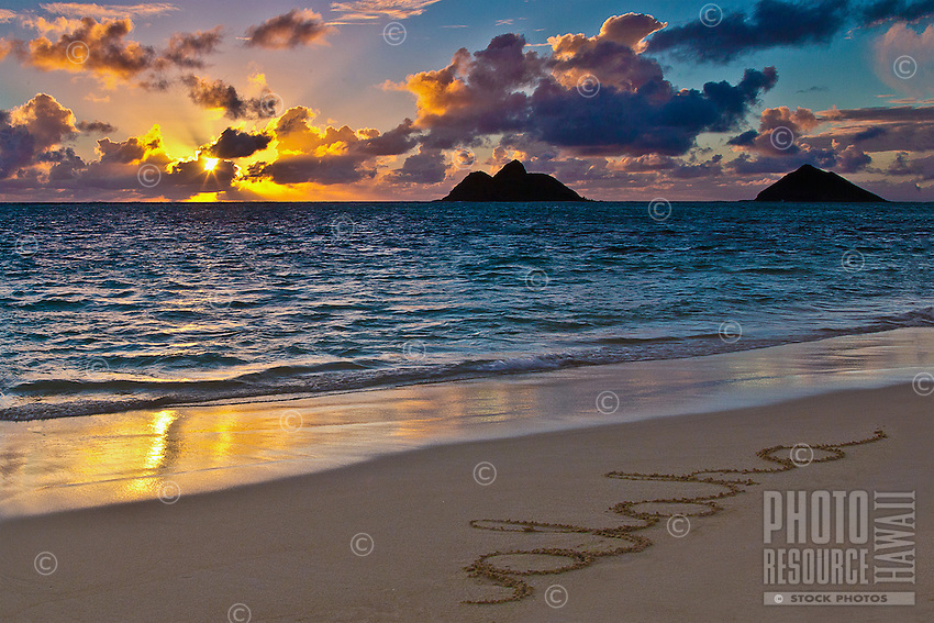 """Rays from the rising sun reflect in the water off of Lanikai Beach, Windward O'ahu; the word """"aloha"""" marks the smooth sand beach in the foreground."""