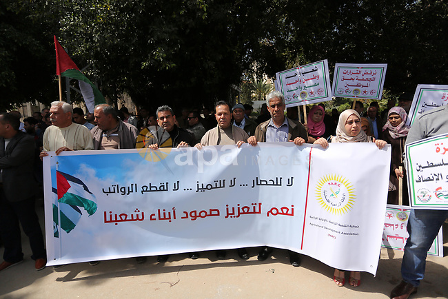 Palestinians employed by the Palestinian Authority, chant slogans and wave placards during a demonstration against the decision to reduce their salaries in Gaza City on April 11, 2017. Photo by Ashraf Amra