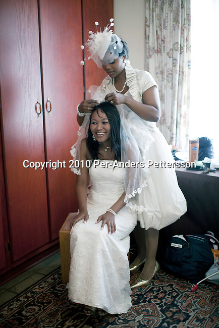 JOHANNESBURG, SOUTH AFRICA - MAY 1: Siphokazi Cola, age 26, is prepared for her wedding ceremony by her friends and outside a church chapel as she celebrate her wedding day with Xolile Ngambane, age 28, at the Tuscan Wedding village on May 1, 2010, in Johannesburg, South Africa. Newly rich black entrepreneurs, such as this couple, love to throw lavish Western styled white weddings for hundreds of people. This Tuscan wedding theme village venue has a waiting list for two years. The couple went through a traditional and colorful wedding the following day at home. (Photo by Per-Anders Pettersson)