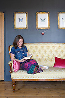 Designer Hannah Pemberton photographed relaxing on a restored sofa in the grey-painted living room of her Victorian terraced house in Nottingham