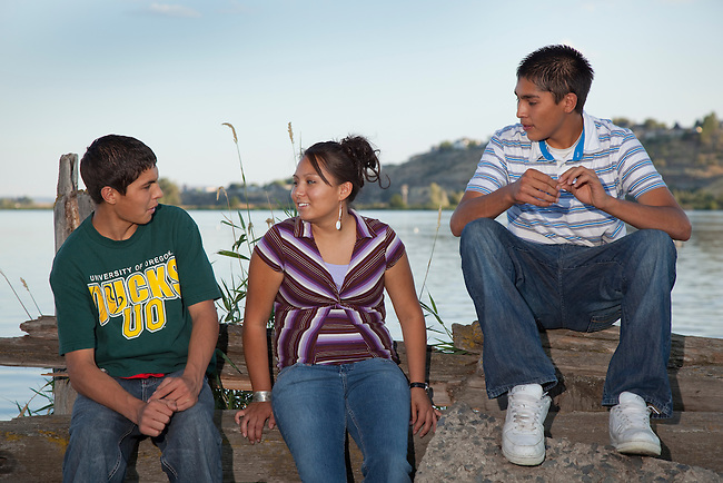 Three Native American teenagers talk while they hang out together on Klamath Lake, Oregon