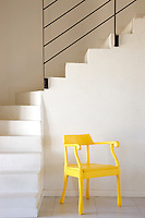 At the foot of the simple curved staircase sits a bright yellow Jens Fager armchair