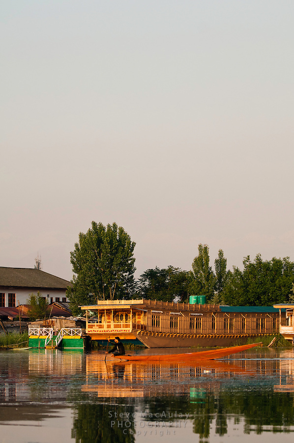 Man paddling a traditional Kashmiri shikara, or gondola, past a houseboat at sunrise, Dal Lake, Srinagar, Kashmir, India..