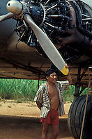 Relationship between Yanomami indigenous people and independent mine workers called garimpeiros who invaded the indigenous territory, Roraima State, Amazon rainforest, Brazil. Out of order aircraft under service of the mining industry parked at indigenous land for repair.