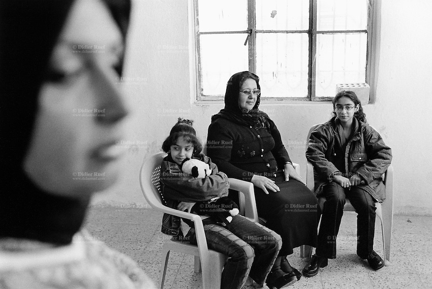 Iraq. Baghdad. Iraqi women league. Portrait of Um Likaas and her two daughters. Her husband was killed in 1994 by the regime of Saddam Hussein. Women wear the hijab on their head which covers the hair. The word hijab (or hidjab) refers to the veil covering the head traditionally worn by muslim women. Islamic headscarf. 20.02.04 © 2004 Didier Ruef .