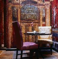 A faux frieze depicting aged and distressed trompe l'oeil classical architecture covers the walls of the breakfast room