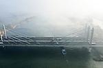 Foto: VidiPhoto<br /> <br /> HERVELD – De Tacitus(tui)brug (A50) tussen het Betuwse Herveld en Ewijk in het Land van Maas ren Waal maandag, terwijl flarden mist wegtrekken. De Betuwe had maandag last van een hardnekkige mist die voor de nodige verkeersoverlast zorgde. Ook in de nacht van maandag op dinsdag en dinsdag overdag wordt er in grote delen van het land mist verwacht. Daarna overheerst ander herfstweer, met veel regen. De Tacitusbrug is inclusief toeritten en aanbruggen 1055 meter lang, de hoofdoverspanning meet 270 meter. Ruim vijf jaar na de verbreding naar vier stroken in iedere rijrichting, staan er weer regelmatig files bij knooppunt Ewijk.