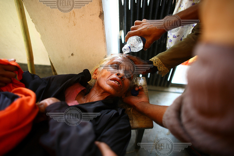 A woman is helped after she fainted whilst waiting to vote in the general elections. The 2008 elections brought an end to almost two years of emergency rule in Bangladesh with a landslide victory for the Awami League-led grand alliance, which won 263 of the 300 available seats.
