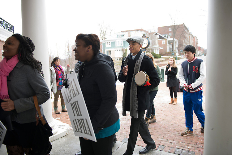 Mike Jones a freshman studying Business Economics plays a drum while walking into Baker Center at the conclusion of a silent march held on Martin Luther King Day. (Photo by Olivia Wallace)