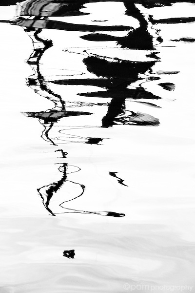 Monochrome reflection of dock in moving water