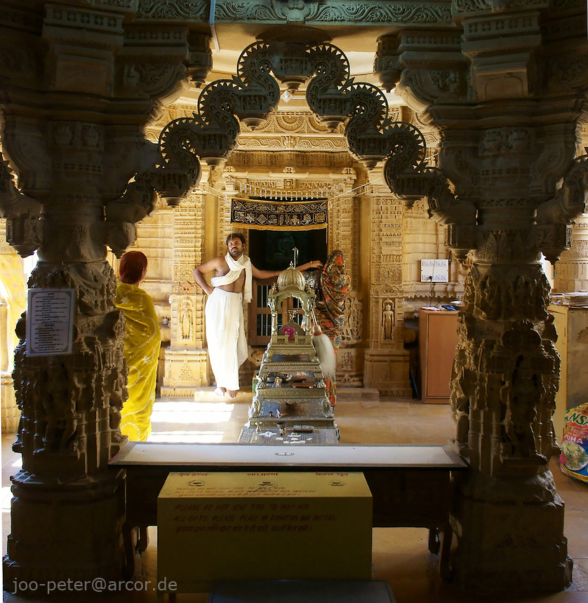 main room in Chantraprabhu Jain temple  in Fort Jaisalmer, Rajastan, India. Worshippers arrive for praying in front of the main shrine in the centre