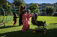 "January 10, 2015 - Rawang (Malaysia). Two small girls push a stroller in the park inside the ""Global Ikhwan village"", a compound of commercial and residential estates owned by the organization in Rawang, a small town in the north of Kuala Lumpur. © Thomas Cristofoletti / Ruom"