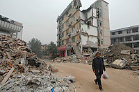 A local resident picks his way through the rubble of Dujiangyan..17 May 2008