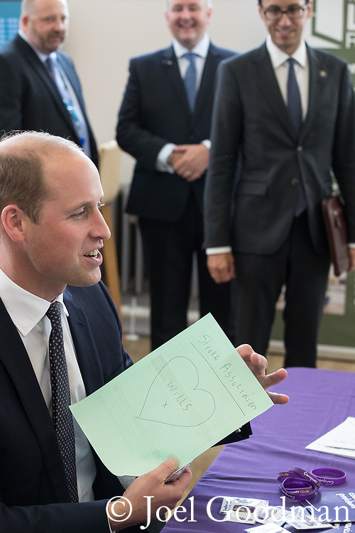 "© Joel Goodman - 07973 332324 - all rights reserved . NO ONWARD SALE OR SYNDICATION PERMITTED - ONLY FOR USE IN REPORTING THE LIVE STORY TO WHICH THE PHOTOGRAPH IS RELATED . 14/09/2017 . Liverpool , UK . The Duke of Cambridge , Prince William , sits in front of a sheet of paper with "" Wills "" and a heart and kisses written on it , left by women from the Stroke Association , during a visit to Life Rooms in Walton . Life Rooms provides community support to help people recover from mental health issues . Photo credit : Joel Goodman"