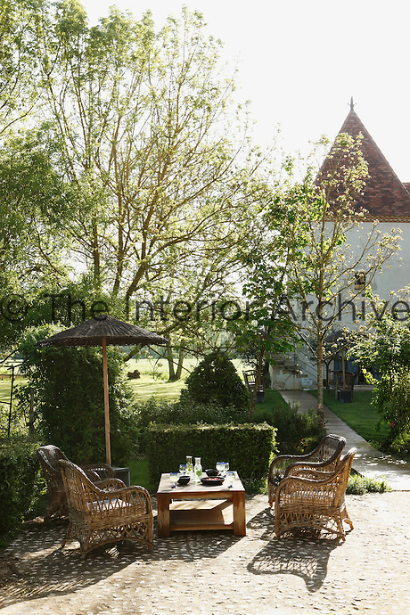 A secluded corner of the garden with a view of the turreted pigeonnier is furnished with a teak table and rattan armchairs by Sarah Lavoine