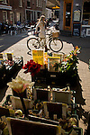 A woman on a bike walks past the floating flower market in Amsterdam.
