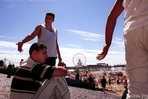 """British Muslim """"Plastic Gangsters"""" from Bradford hang out at a beach in Blackpool. ..A generation of Muslims is growing up separated from the indigenous society. They go to predominantly Asian schools and hang out with Asian friends. Often the only contact between the two communities is through uncertain glances on the street or in local tabloids. Stuck in a Western society but feeling unwelcome and without many chances to escape from the ghetto, many youngsters seek identity in Islam...Photo by Justin Jin. Northern England, August 2001."""