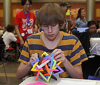 Aaron Pfitzenmaier folding a modular origami design between classes