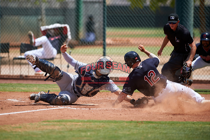 AZL Indians Red catcher Yainer Diaz (4) attempts to apply the tag as Ike Freeman (12) reaches to touch home plate during an Arizona League game against the AZL Indians Blue on July 7, 2019 at the Cleveland Indians Spring Training Complex in Goodyear, Arizona. Home plate umpire Bailey Dutten ruled Freeman out on the tag. The AZL Indians Blue defeated the AZL Indians Red 5-4. (Zachary Lucy/Four Seam Images)