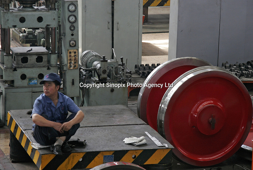 A Chinese worker sits near a set of locomotive wheels at the state-owned Datong Electric Locomotive Co. LTD in Datong, Shanxi Province, China. China's developing economy has created a huge demand for faster and more powerful locomotive engines to move its people and goods within its vast and expanding railway network, the Datong company is currently working together with several western partners including Alstom of France and ABC of the U.S..05 Jul 2005