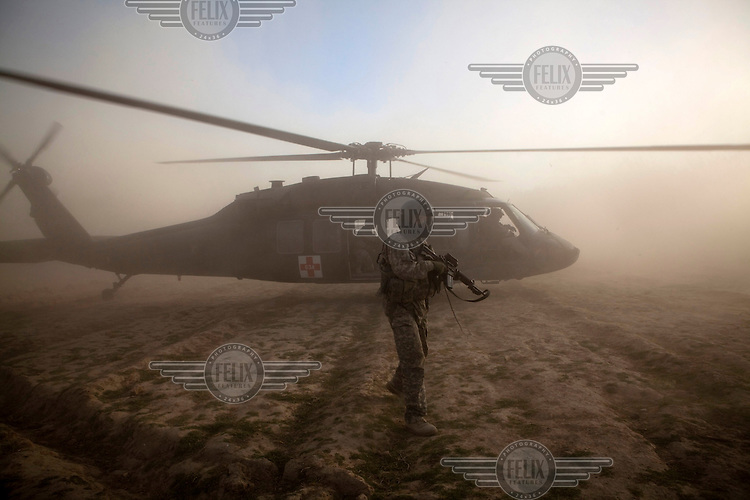 A US Army crew chief secures the landing zone after a medevac helicopter from Charlie Company, Sixth Battalion, 101st Aviation Regiment landed in the middle of a firefight to evacuate wounded US soldiers near Kandahar.