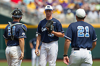 North Carolina pitcher Trent Thornton (31) waits on the mound before talking with catcher Brian Holberton (10) and pitching coach Scott Forbes (21) during Game 7 of the 2013 Men's College World Series  against the Louisiana State Tigers on June 18, 2013 at TD Ameritrade Park in Omaha, Nebraska. The Tar Heels defeated the Tigers 4-2, eliminating LSU from the tournament. (Andrew Woolley/Four Seam Images)