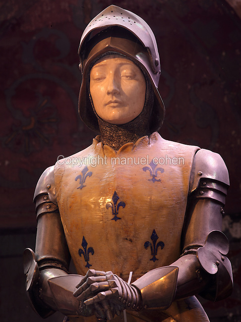 Statue of Joan of Arc, 'Jehanne au sacre', 1901, by Prosper d'Epinal, in an apsidal chapel in the Cathedrale Notre-Dame de Reims or Reims Cathedral, Reims, Champagne-Ardenne, France. Her armour is bronze, her face ivory, and her tunic is yellow marble with fleurs de lys incrusted with lapis lazuli. The cathedral was built 1211-75 in French Gothic style with work continuing into the 14th century, and was listed as a UNESCO World Heritage Site in 1991. Picture by Manuel Cohen