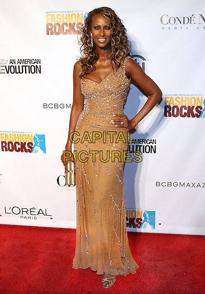 IMAN.2005 Fashion Rocks held at the Radio City Music Hall.New York.USA, United States.8th September 2005.Ref: ADM/JL.full length gold bronze fitted floor length dress sequin sequinned off the shoulder hand on hip curls curly ringlets posed.www.capitalpictures.com.sales@capitalpictures.com.© Capital Pictures.
