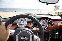 Dashboard and steering wheel of convertible MINI Cooper with beach background showing Hawaii's scenic drive on the South Shore of Oahu