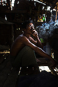 60 year old Maung Ko smokes a Cherod, a Burmese Cigar in his hut in Damin Naung village in Pyapon district of Myanmar. Maung is a crab fisherman and makes an average of $5/day - he only works 14 days a month.