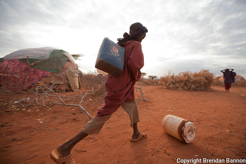 A young girl rolling a container of water home while carrying two jerry cans of water on her back in the informally settled area surrounding Ifo camp, one of the three camps surrounding the Kenyan Town of Dadaab.