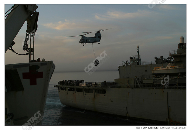 "A supply ship  delivers food, and other supplies to the Comfort via a ""vertical drop"" where helicopters go back and forth lifting palets from the supply ship and dropping them onto the comfort. The supply ship also delivered fuel. The opertaion takes several hours, and if medevacs come in, they need to halt the vertical drop. USNS COMFORT Naval hospital ship in the Persian Gulf."