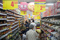Shoppers walk through a crowded aisle in a hypermarket in Nanjing, Jiangsu, China.