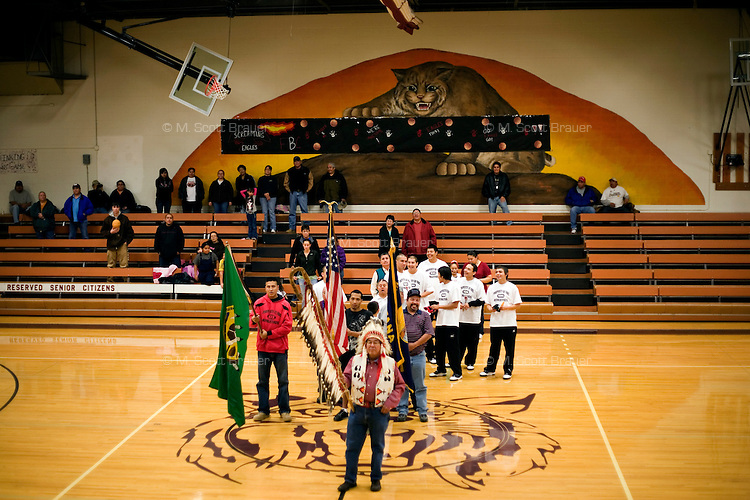 Hal Chandler Goodstrike carries the Eagle Staff leading a procession of veterans and the Fort Belknap College Eagles during the opening ceremony of the 2010 Fort Belknap College Round Robin Tournament at Harlem High School in Harlem, Montana, USA.