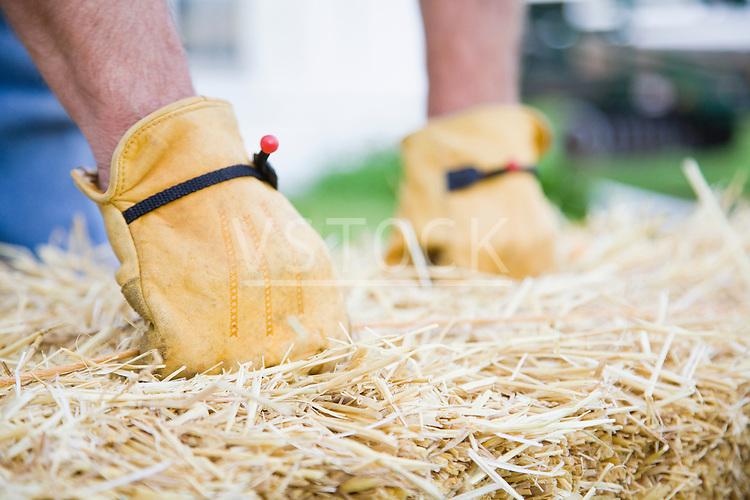 USA, Illinois, Metamora, Farmer lifting hay bale on farm