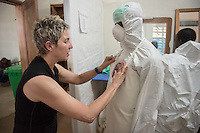 "Occidental College professor Mary Beth Heffernan applies an adhesive portrait to David Selma, hygienist before Selma enters the ""red zone"" to care for unconfirmed Ebola patients in the ELWA II ETU (Ebola treatment unit), Monrovia, Liberia on March 12, 2015. Heffernan's PPE Portrait Project involves creating wearable portraits of the health care workers who must wear PPE (personal protective equipment) when working with patients.<br /> (Photo by Marc Campos, Occidental College Photographer) Mary Beth Heffernan, professor of art and art history at Occidental College, works in Monrovia the capital of Liberia, Africa in 2015. Professor Heffernan was there to work on her PPE (personal protective equipment) Portrait Project, which helps health care workers and patients fighting the Ebola virus disease in West Africa.<br />